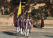 Actors play American militia carrying guns, flags, drum and fife outside of the Capitol building at Colonial Williamsburg, Virginia. A black woman in brown cape looks on. Colonial Williamsburg is the historic district of the independent city of Williamsburg, Virginia, which was colonial Virginia's capital from 1699 to 1780, and a center of education and culture.