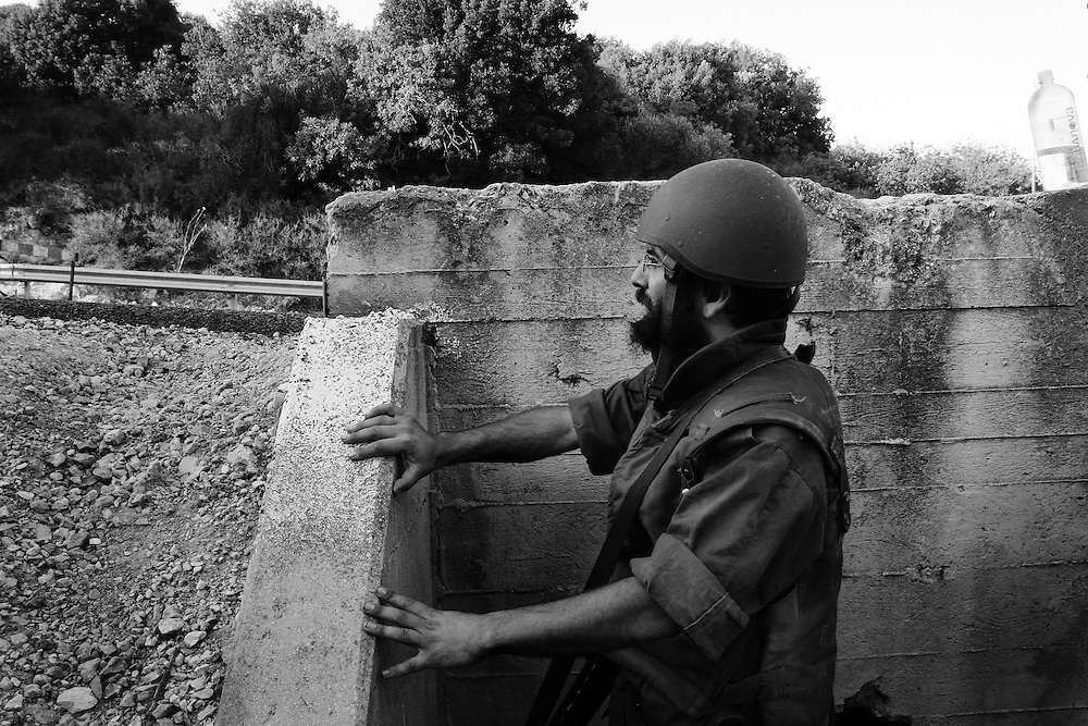An Israeli reservist soldier looks out from a bunker during a Hezbollah rocket attack. Aug 2006