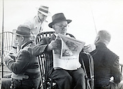 senior man reading newspaper while other people are fishing USA 1940s
