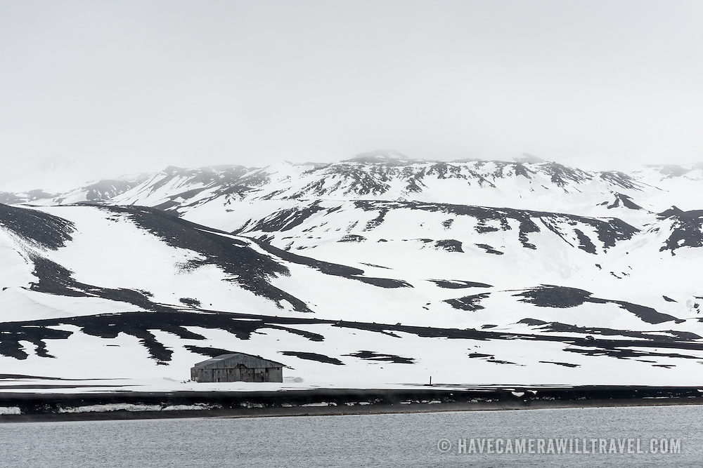 An abandoned aircraft hangar at the former whaling station at Whalers Bay on Deception Island. Deception Island, in the South Shetland Islands, is a caldera of a volcano and is comprised of volcanic rock.