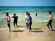 "13 FEBRUARY 2019 - SIHANOUKVILLE, CAMBODIA: Chinese tourists on Ocherteal Beach in Sihanoukville. There are about 80 Chinese casinos and resort hotels open in Sihanoukville and dozens more under construction. The casinos are changing the city, once a sleepy port on Southeast Asia's ""backpacker trail"" into a booming city. The change is coming with a cost though. Many Cambodian residents of Sihanoukville  have lost their homes to make way for the casinos and the jobs are going to Chinese workers, brought in to build casinos and work in the casinos.      PHOTO BY JACK KURTZ"
