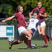 UNCW's Karissa Smith passes the ball through the legs of Elon's Grace Bennett Sunday October 5, 2014. (Jason A. Frizzelle)