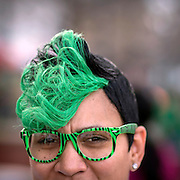 Tiffany Monday of Eatonton, Ga dyed her hair green for her first St. Patrick's celebration as she hangs out with friends on River Street, Saturday, March 14, 2015, in Savannah, Ga. The most recent economic impact study, conducted back in 2001, found St. Patrick's visitors spent $30 million just at the bars, restaurants and merchants along the city's popular riverfront. (AP Photo/Stephen B. Morton)