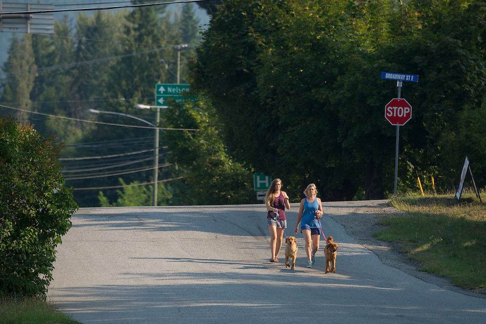 Canada, British Columbia,Nakusp,Upper Arrow lake, women walking dog