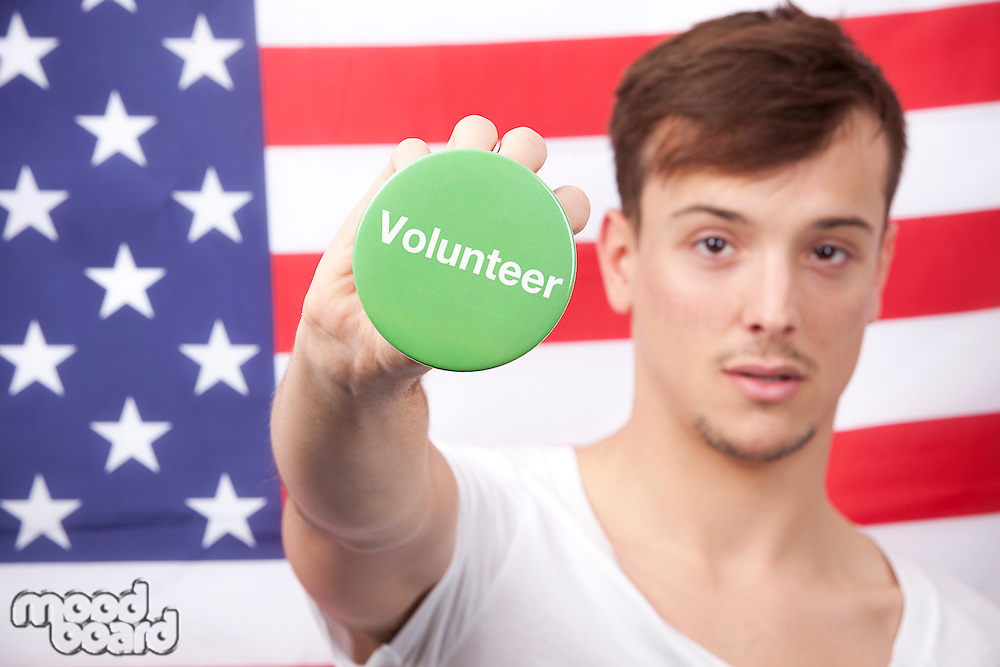 Portrait of young man displaying volunteer badge against American flag