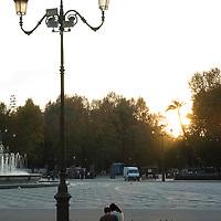 A couple sitting on a bench in the Plaza de España, Sevilla, Andalucia, Spain.