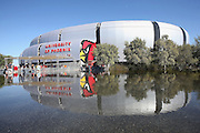 Fans pass through the security check while the University of Phoenix Stadium reflects in a reflecting pool in this general view photograph of the stadium exterior taken before the Arizona Cardinals 2015 NFL preseason football game against the San Diego Chargers on Saturday, Aug. 22, 2015 in Glendale, Ariz. (©Paul Anthony Spinelli)