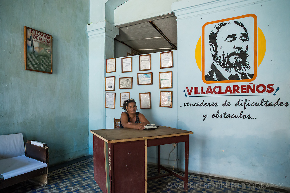 A woman sits at a desk of a government office of Santa Clara council. On the wall in the back a series of acknowledgments for the excellence of the services offered and a propaganda poster about the philosophy of the fight. Santa Clara. Cuba, 2015.