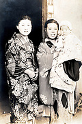 young mother holding baby casual posing with friend Japan ca 1940s