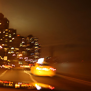 An image of a yellow New York Taxi cab showing motion and movement as it navigates through the city lights and metropolis of the big city at night time. New York, USA. 26th October 2012. Photo Tim Clayton