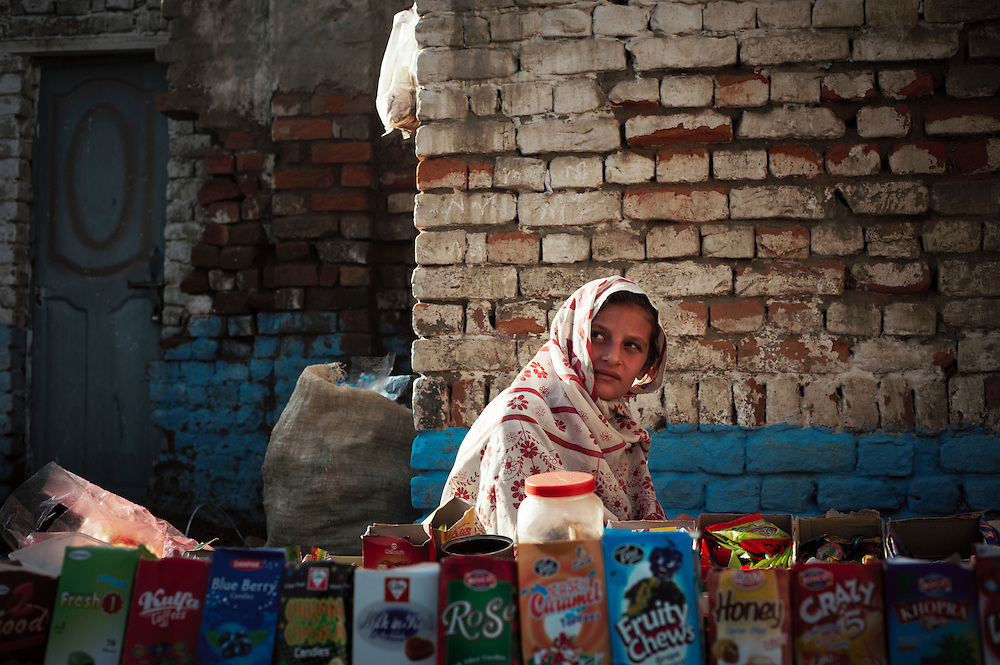 Pakistan/ Afghan refugees/ A girl sells snacks in the Khazana refugee camp, Peshawar. The camp was established when refugees flooded across the border from Afghanistan during the 1979 Soviet occupation. The refugee camp has a population of 2500 and during the 2010 floods that swept through Pakistan most families were affected. The majority of people rebuilt their houses after the floods with their own resources. The most vulnerable also received support from UNHCR for reconstruction. UNHCR/Sam Phelps/ November 2011.