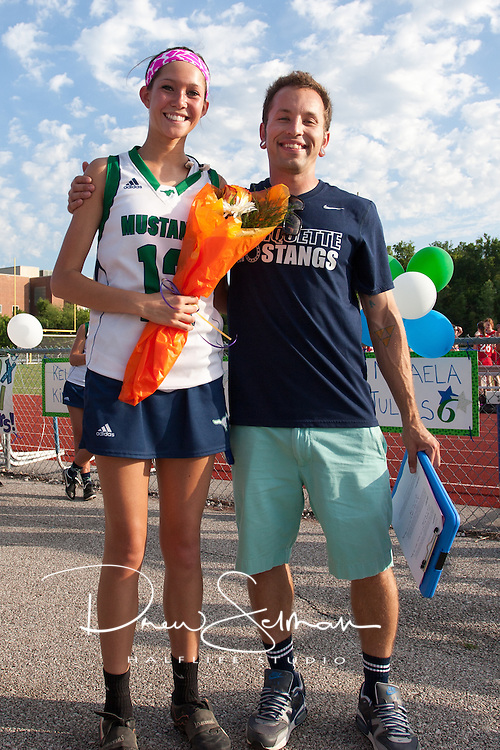 Marquette High School Senior Lacrosse player, Carolyn Roseberry (12) is honored at halftime against Barat Academy. Coach Chris Elledge, also pictured, read a short bio of each player.  Marquette won the game 15 to 0.