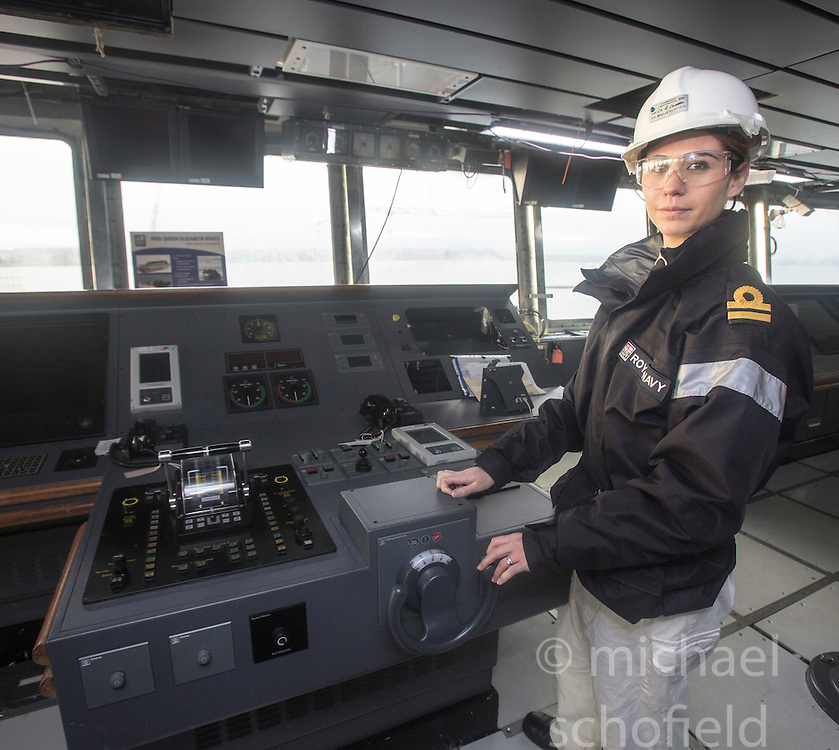 Lt Rachel Campbell, deputy navigator at the ships steering wheel the bridge during the tour of the Queen Elizabeth Aircraft Carrier under construction at the Babcock site in Rosyth dockyard.