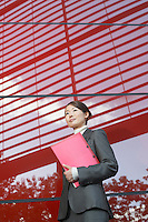 Businesswoman holding notebook Standing Beside red Building low angle view