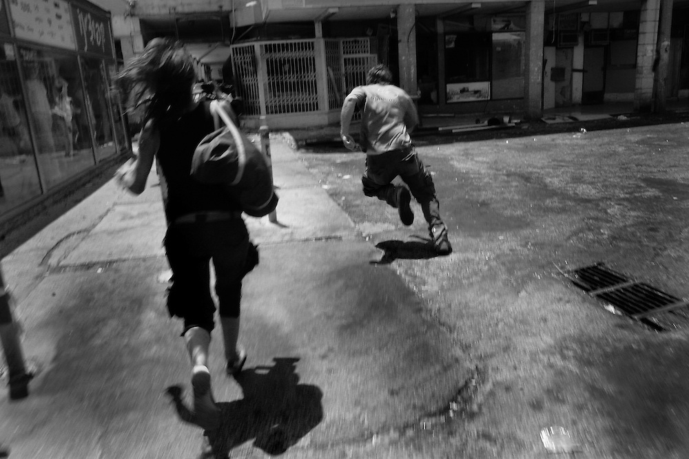 People run for cover in central Kiyrat Shmona as the air raid siren signals another Hezbollah rocket attack. Aug 2006