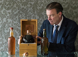 Bonhams whisky sale in Edinburgh on 7 June includes two salvaged bottles from the wreck of the SS Politician which were the inspiration for Compton MacKenzie's novel Whisky Galore. Also included in the sale is a 50 year-old Macallan Millennium Decanter distilled in January 1949.<br /> <br /> Pictured: Bonham's Whisky Consultant, Martin Green with Gilbey's - circa 1940 estimate &pound;6,000 - &pound;8,000, The Macallan Millennium Decanter - 50 year-old estimate &pound;15,000 - &pound;17,000 and Peter Dawson - circa 1940 estimate &pound;4,000 - &pound;6,000