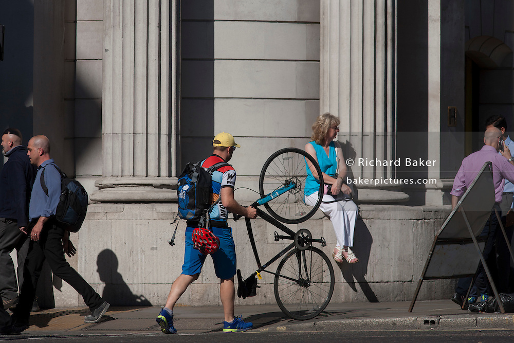 A cyclist pushes his upright bike on its rear wheel on the pavement at Bank station in the heart of London's financial heart, the City of London, UK.
