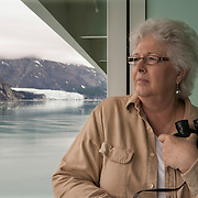 Valerie More looks at glaciers from her private balcony on board the Norwegian Pearl, a cruise ship of Norwegian Cruise Line at Glacier Bay National Park. Photography by Jose More<br />  MR Model Release