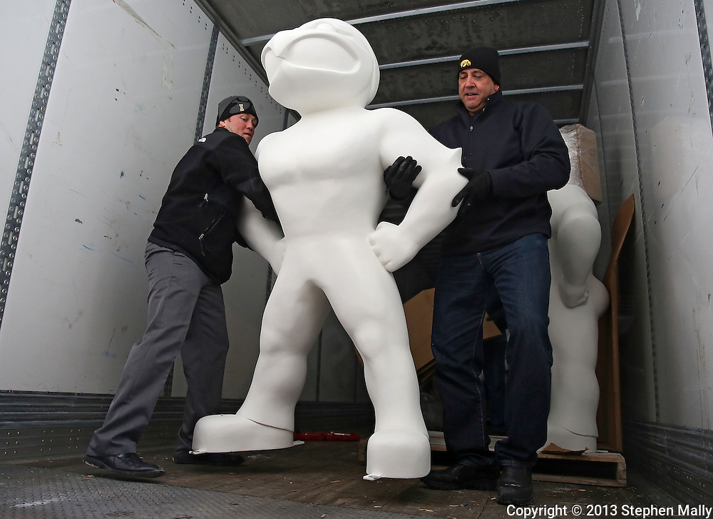 Nick Kaeding (from left), Director of Finance for the Iowa City/Coralville Area Convention & Visitors Bureau, and Dale Arens, Director of University of Iowa Hall of Fame and Licensing, move the first statue to the end of the truck as they unload the first shipment of 20 Herky On Parade statues in Coralville on December 12, 2013.