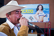 July 25 - PHOENIX, AZ: MARTIN MIRAMONTES, a Mexican national who has been in the US for 10 years, sings karaoke in a bar at El Gran Mercado in Phoenix. El Gran Mercado (The Big Market) in Phoenix is the largest flea market in the Phoenix area and has served the area's immigrant community for more than 20 years. With more than 150 small independent stalls selling Mexican clothes, cowboy hats, Mariachi music and food stalls selling Mexican favorites like birria chivo (goat stew) and menudo (tripe) it was more like a Mexican market than an American mall. Business in the mercado is down more than half this year because many immigrant families, legal and illegal, are leaving Arizona before the state's tough new anti-immigrant law, SB 1070 goes into effect on July 29. SB 1070 allows local police officers to check the immigration status of people they have probable cause to believe may be in the US illegally and requires immigrants to carry their immigration papers with them at all times.    Photo by Jack Kurtz