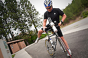 Marc Ellingsen of Rathdrum hops on his bike for a training ride on the Centennial Trail past the Potlatch Hill Road overpass in Coeur d'Alene on Wednesday afternoon.