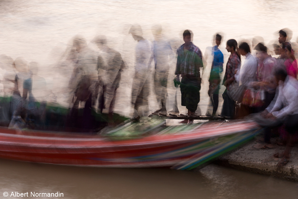 Blur of crowd of people boarding a commuter boat to cross Yangon river, Yangon