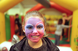 Teenage girl at youth club with face painted; children on bouncy castle in background,