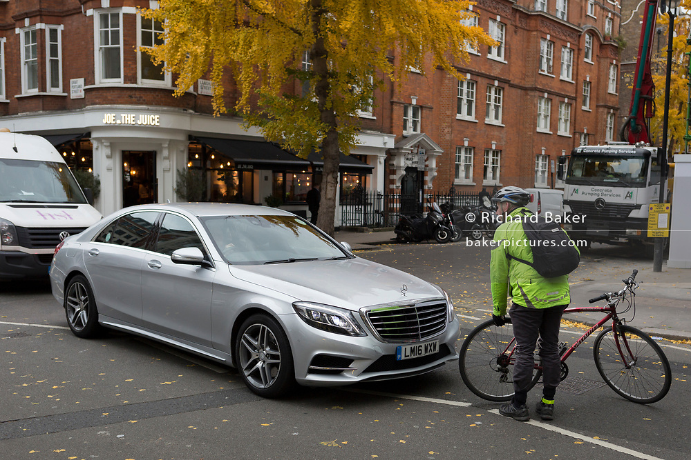 An annoyed cyclist stops to confront a motorist and very slowly check his bike over for any damage after a Mercedes driver nudged his rear wheel in frustration of heavy traffic, on 22nd November 2017, in London England.
