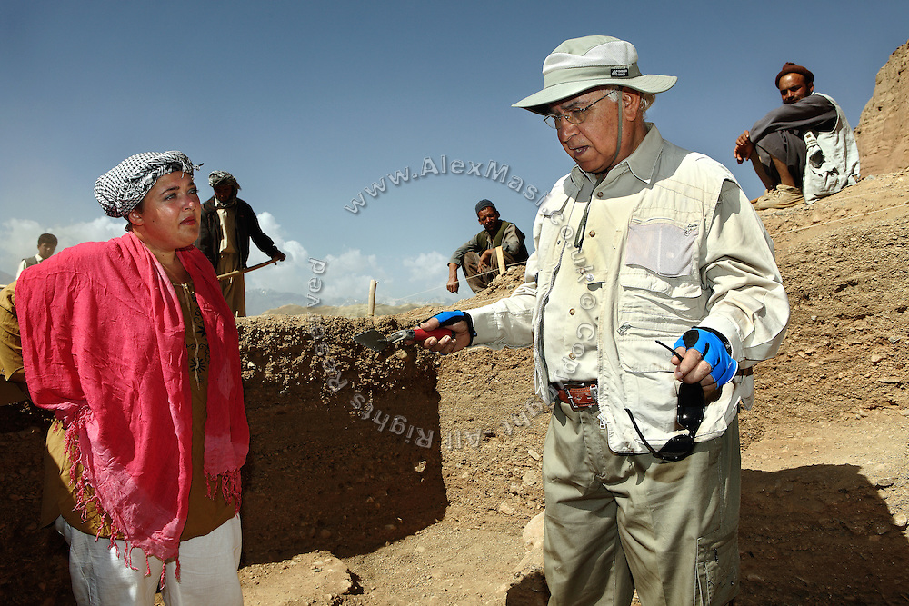Professor Zemaryali Tarzi, (right) a notable An Afghan-born archaeologist from France and teacher in Strasbourg University, is portrayed discussing with one of his assistants on the excavation field where he is searching for a legendary 300m Sleeping Buddha. The statue should be located between the original two standing Buddhas, Afghanistan, as documented in the old account of a renowned Chinese scholar, Xuanzang, visiting the area in the 7th century. The Buddhas of Bamiyan were two 6th century monumental statues of standing Buddhas carved into the side of a cliff in the Bamiyan valley in the Hazarajat region of central Afghanistan, situated 230 km northwest of Kabul at an altitude of 2500 meters. The statues represented the classic blended style of Gandhara art. The main bodies were hewn directly from the sandstone cliffs, but details were modelled in mud mixed with straw, coated with stucco. Amid widespread international condemnation, the smaller statues (55 and 39 meters respectively) were intentionally dynamited and destroyed in 2001 by the Taliban because they believed them to be un-Islamic idols. Once a stopping point along the Silk Road between China and the Middle East, researchers think Bamiyan was the site of monasteries housing as many as 5,000 monks during its peak as a Buddhist centre in the 6th and 7th centuries. It is now a UNESCO Heritage Site since 2003. Archaeologists from various countries across the world have been engaged in preservation, general maintenance around the site and renovation. Professor Tarzi worked on projects to restore the other Bamiyan Buddhas in the late 1970s and has spent most of his career researching the existence of the missing giant Buddha in the valley.