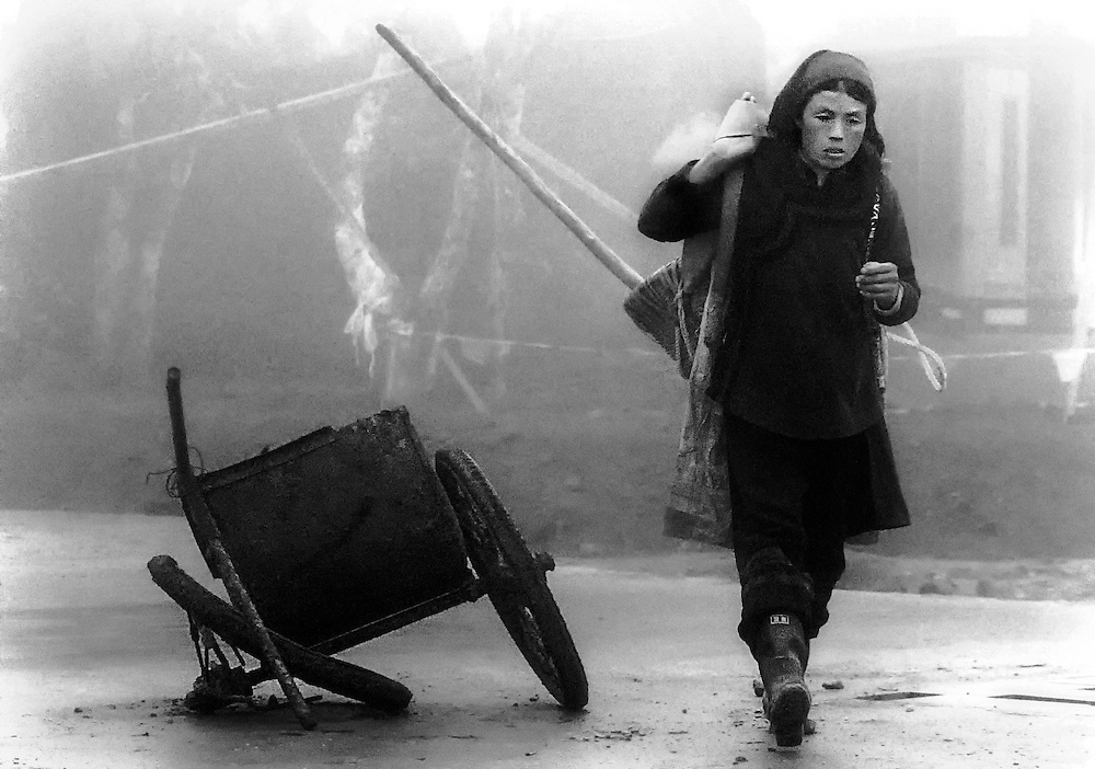 A woman working on a road in the early morning mist in Yuanyang, China.