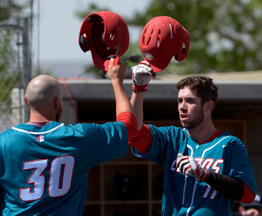 gbs032217u/SPORTS -- UNM's Andrew Pratt, 11, taps helmets with Carl Stajduhar, 30, after he hit a home run in the first inning of the game against Grand Canyon University at the Santa Ana Star Field on Wednesday, March 22, 2016. (Greg Sorber/Albuquerque Journal)