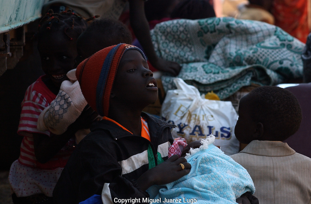 10 year old, Juma Kual, holds the Ismail Gabriel, days old, as he looks for the mother of the baby, lost momentarly in the confussion on getting register.  More then 50 thousand south sudanese people has used the cross point of the city of Malakal to return to and resettle in their country as more of them Independence is emminent. (PHOTO: MIGUEL JUAREZ).