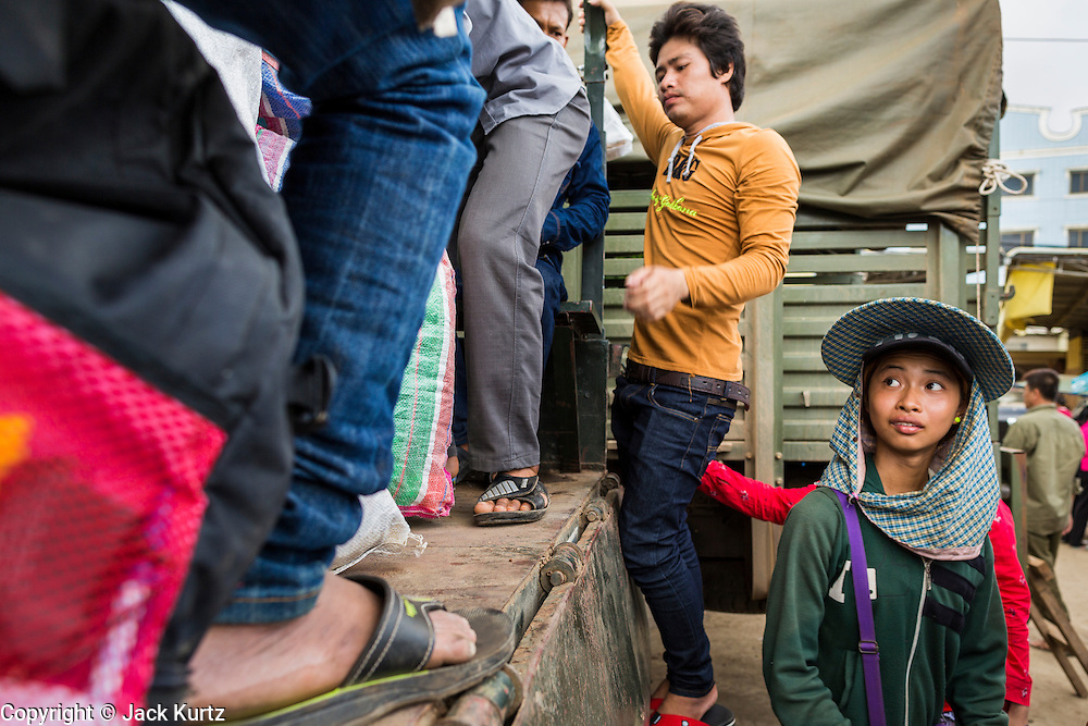 16 JUNE 2014 - POIPET, CAMBODIA: Cambodian migrants look for space in an army truck in Poipet, Cambodia after they returned to Cambodia from Thailand. More than 150,000 Cambodian migrant workers and their families have left Thailand since June 12. The exodus started when rumors circulated in the Cambodian migrant community that the Thai junta was going to crack down on undocumented workers. About 40,000 Cambodians were expected to return to Cambodia today. The mass exodus has stressed resources on both sides of the Thai/Cambodian border. The Cambodian town of Poipet has been over run with returning migrants. On the Thai side, in Aranyaprathet, the bus and train station has been flooded with Cambodians taking all of their possessions back to Cambodia.  PHOTO BY JACK KURTZ