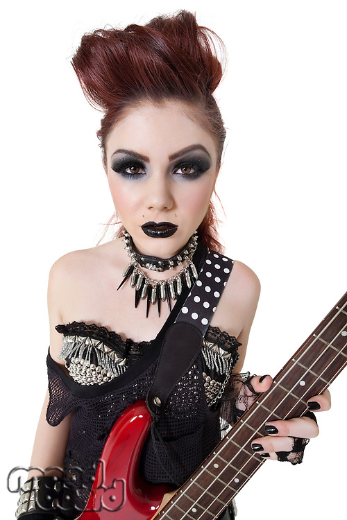 Portrait beautiful punk woman staring while holding guitar over white background