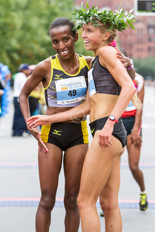 Tufts Health Plan 10K for Women Jordan Hasay wears winner's laurel wreath after running 31:38, congratulated by runner-up Caroline Rotich
