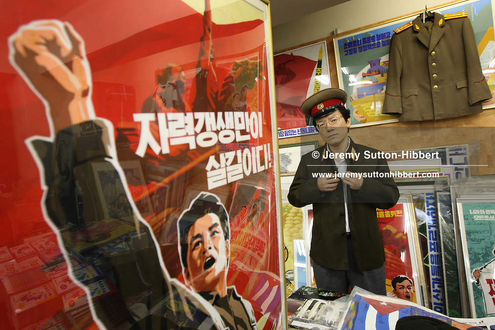 """Mr. Jun Miyagawa, of the Rainbow Trading Company ( a North Korean speciality bookstore) wears a new, and genuine,  North Korean military uniform and hat whilst showing off the North Korean products he has for sale ( including Kim Il Sung badges, North Korean bank notes, football memorabilia, cigarettes, and North Korean propaganda posters and genuine North Korean military uniforms), in his book store in Jimbocho district,  Tokyo, Japan, Friday, Aug. 17, 2007. All the products come via a contact of Mr Miyagawa's in China. The posters are individually painted and range in price from ¥50,000-¥150,000, the Kim Il Sung badges cost approximately JPN Yen 4,000. The products are bought mainly by Japanese 'North Korea fans"""", or as Mr. Miyagawa put it """"by Japanese who have a healthy obsession with North Korea""""."""