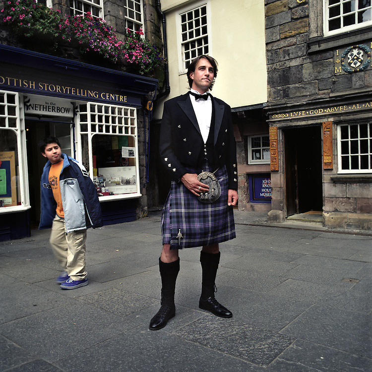 Scottish DJ, Andy Niven, wearing a Prince Charlie kilt from 21st Century Kilts, on Edinburgh's Royal Mile, Scotland, UK..