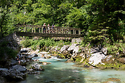 Visitors look from the bridge over the Tolminka river while others sit underneath at Tolminska Korita, on 20th June 2018, in Tolmin Gorge, Slovenia.