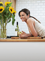 Young woman drinking wine leaning on kitchen counter
