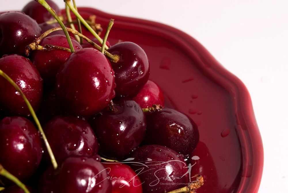 Fresh Bing cherries are served on a burgundy plate. Cherries are not only a low-fat snack, but they are also high in antioxidants. (Photo by Carmen K. Sisson/Cloudybright)