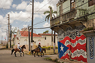 Men on horseback lead their horses down a side street on Tuesday, April 17, 2018 in Mayagüez, Puerto Rico. LCMS Communications/Erik M. Lunsford