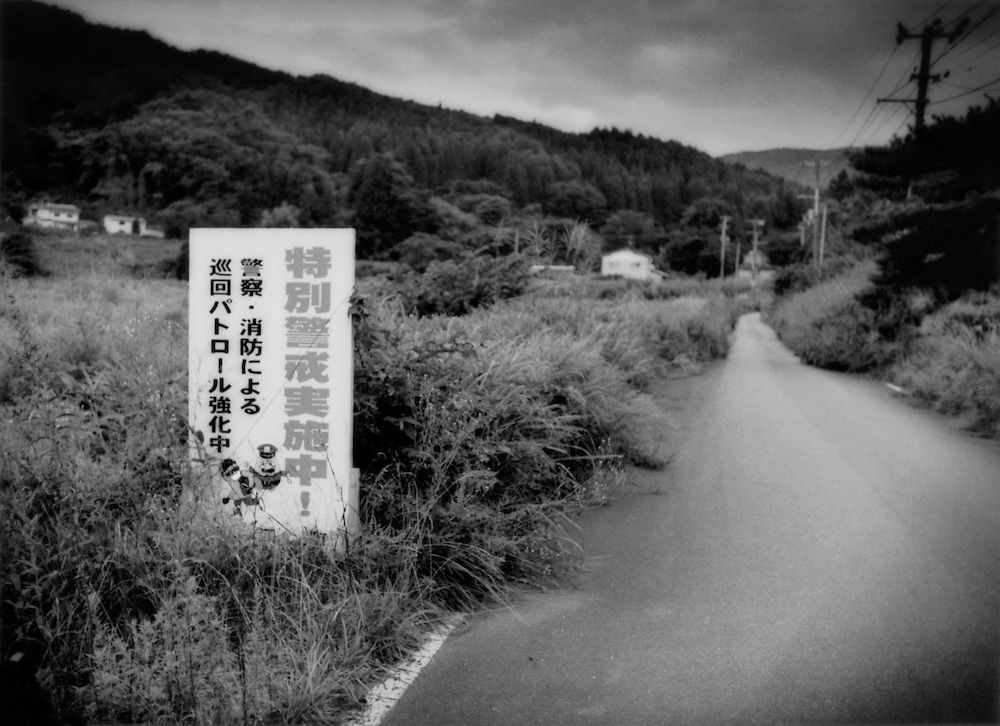 Burglary is a major problem, as the sign warning burglars away indicates, in evacuated villages in Fukushima's nuclear zones.  Decontamination has not even begun here because, according to the Education, Culture, Sports, Science and Technology Ministry, Tsushima will be exposed to annual radiation of more than 50 milli-seiverts (a normal annual dose of radiation from natural sources in 2.4 milli-seiverts).  Tsushima, Namie-machi, Fukushima Prefecture, Japan.