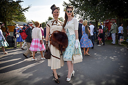 © licensed to London News Pictures. 12/09/2015<br /> Goodwood Revival Weekend, Goodwood, West Sussex. UK.<br /> The Goodwood Revival is the world's largest historic motor racing event. Competitors and enthusiasts dress in period fashions recreating the glorious days of the race circuit.<br /> Pictured. Racegoers in period dress.<br /> <br /> Photo credit : Ian Whittaker/LNP