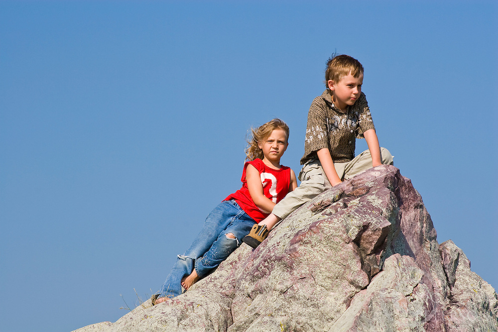 Brother and sister climbing on rocks on a sunny summer day.