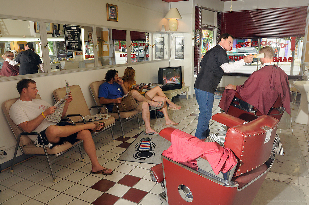 Barber Brent Cox cuts hair with walk-in customers waiting at Woody's Barber Shop on Baxter Avenue near the corner of Highland Avenue Saturday, July 12, 2008 in Louisville, Ky. (Photo by Brian Bohannon/www.brianbohannon.com)