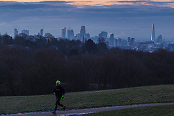 "A man runs through Hampstead Heath as distant clouds brood over the city's skyline. The threatened snow from ""The Beast From The East"" weather system doesn't materialise overnight in London leaving a crisp, clear morning, seen from Hampstead Heath in North London. London, February 27 2018."