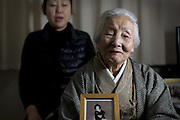 """Kamaishi, Japan - <br /> <br /> Japan 4 Years Later<br /> <br /> On March 11, 2011, a magnitude 9 earthquake struck in the Pacific Ocean about 20 miles off of the Northeastern Japanese coast of Honshu and produced a series of waves, or tsunamis, that reached 30 feet or higher. These waves slammed into a protective seawall built by the Japanese government at an estimated cost of $1.6 billion. The seawalls failed.<br /> <br /> Along the coast, more than 15,000 people lost their lives. 230,000 either lost their homes or were displaced. About 87,000 still live in temporary housing four years later.<br /> <br /> In the temporary housing near Kamaishi, Japan, about half the former residents are gone now. The Japanese government has offered subsidies of $40,000 to $60,000 to help rebuild homes that now cost $300,000 to $450,000 to rebuild, due to the shortage of construction workers and the cost of building materials. Some have moved in with relatives; others moved into permanent apartments and manyhave simply left the area for good.<br /> <br /> Tokyo has set aside $155 billion to rebuild, and yet many in Kamaishi wonder where the money is going. Some of it is spent on schemes to literally raise the ground up to 15 feet in devastated towns like Otsuchi and Rikuzentakata City, which were practically flattened by the tsunami. Even more is being spent to repair the failed seawall.<br /> <br /> Despite efforts by Tokyo to raise the ground level and repair the sea walls, many people in the area are losing hope of having their lives back. Takemi Wada, who lost her home and mother at Rikuzentakata City, said she'll never move back even with the elevated land. """"Who wants to live on top of a graveyard?"""" she asked.<br /> <br /> Photo shows: HIKANO FIJIMA (aka TSUYAKO ITO)  (right), 89, the oldest geisha of Kamaishi and a teacher of traditional Japanese dance, holds a photo of herself as a 28 year-old geisha. Ms. Fujima escaped the tsunami, but lost her home and now has lived in tem"""