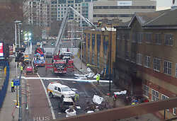 © Licensed to London News Pictures. 17/01/2013. London, UK. As investigators inspect a helicopter part on a roof, wreckage is seen in a road near Vauxhall after a helicopter hit a crane attached to the St George's Wharf development in Vauxhall, London, yesterday (17/01/13). 2 (two) people, including the pilot, died as a result of the incident and a further 11 (eleven) injured after the Augusta 109 helicopter collided with the crane in heavy mist showering wreckage onto cars below. Photo credit: Matt Cetti-Roberts/LNP