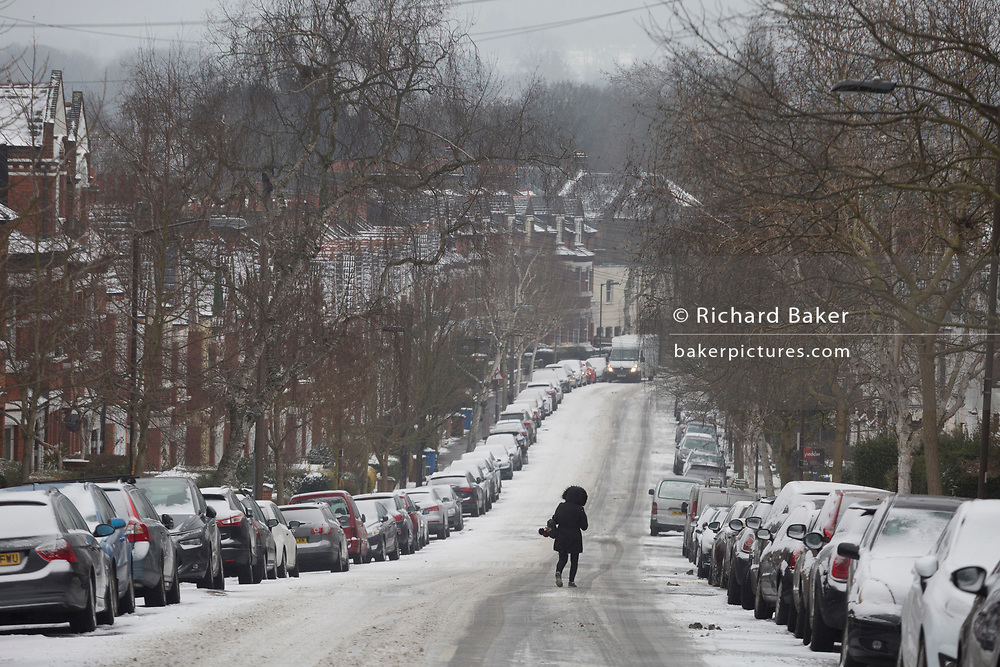 A person crosses an icy minor road in the south London borough of Herne Hill, Lambeth during the bad weather covering every part of the UK and known as the 'Beast from the East' because Siberian winds and very low temperatures have blown across western Europe from Russia, on 1st March 2018, in Lambeth, London, England.