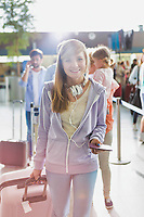 Portrait of young attractive teenage girl holding her passport and suit case at check in area